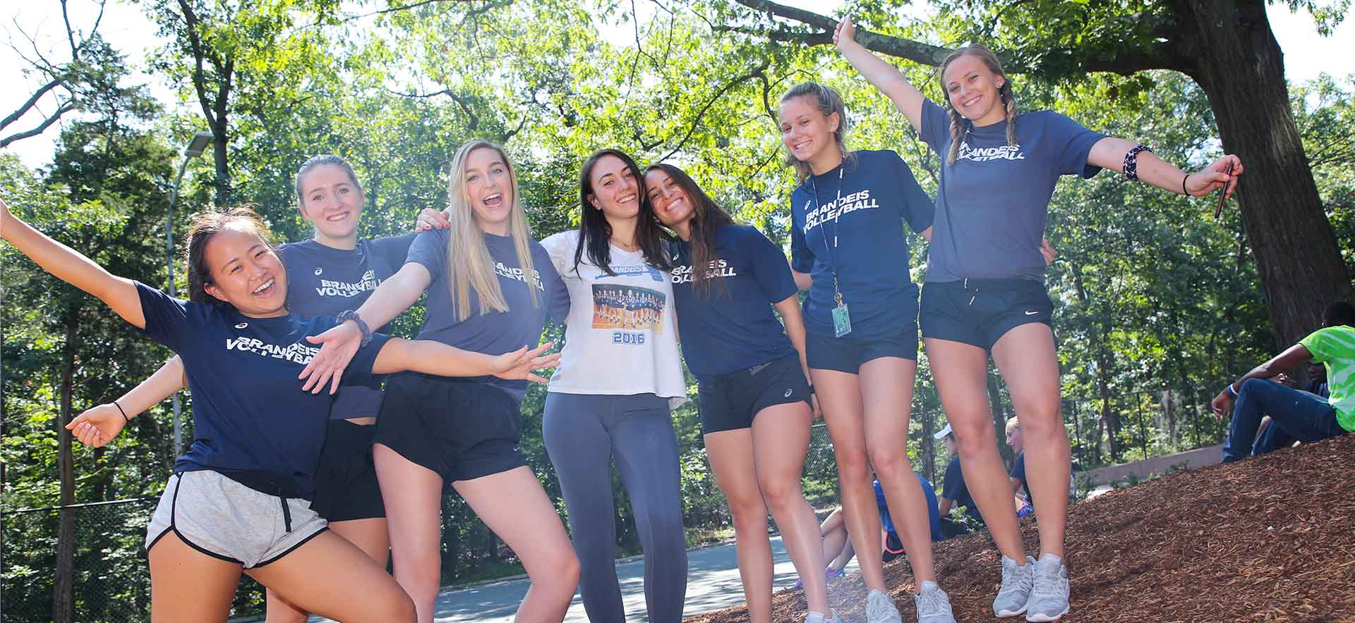 A group of Brandeis student athletes smiling and posing for the camera